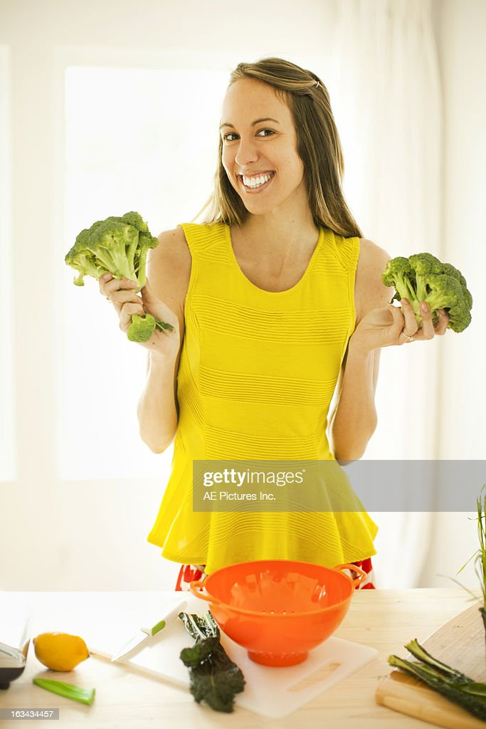 Woman holding broccoli : Stock Photo