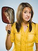 Woman holding broken hand held mirror