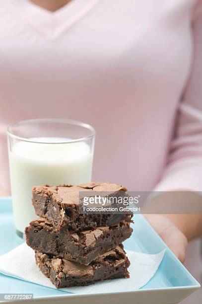 Woman holding brownies and glass of milk on square plate