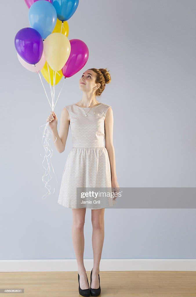 Woman holding bunch of balloons : Stock Photo