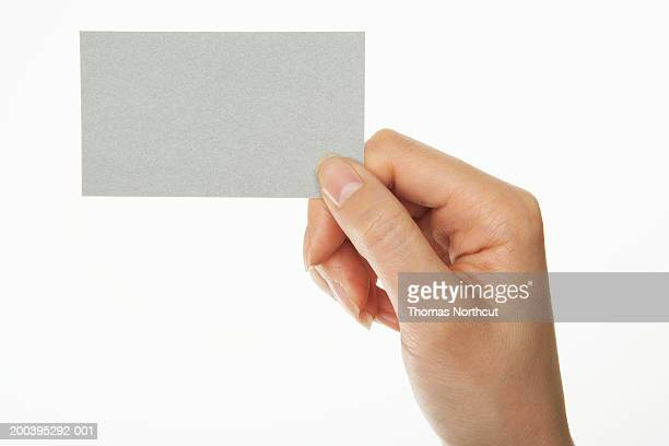 Woman holding business card (focus on business card)
