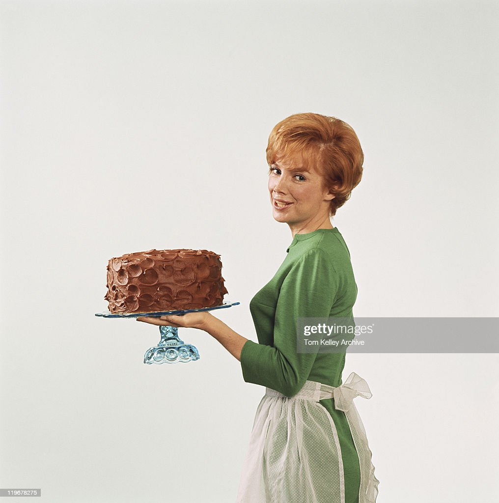 Woman holding cake, smiling, portrait : Unknown