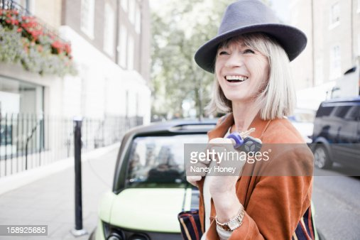 Woman holding car keys on city street