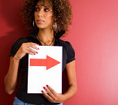 Woman holding card with arrow pointing right