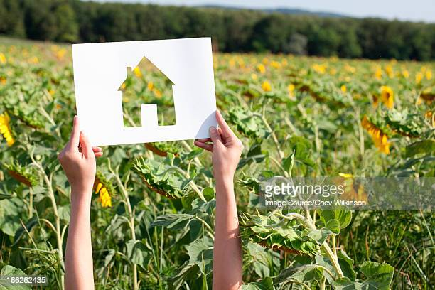 Woman holding card with house shape
