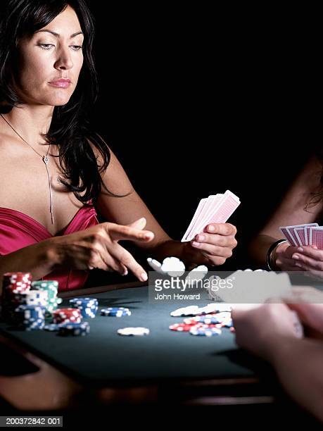 Woman holding cards, throwing gambling chips onto gaming table