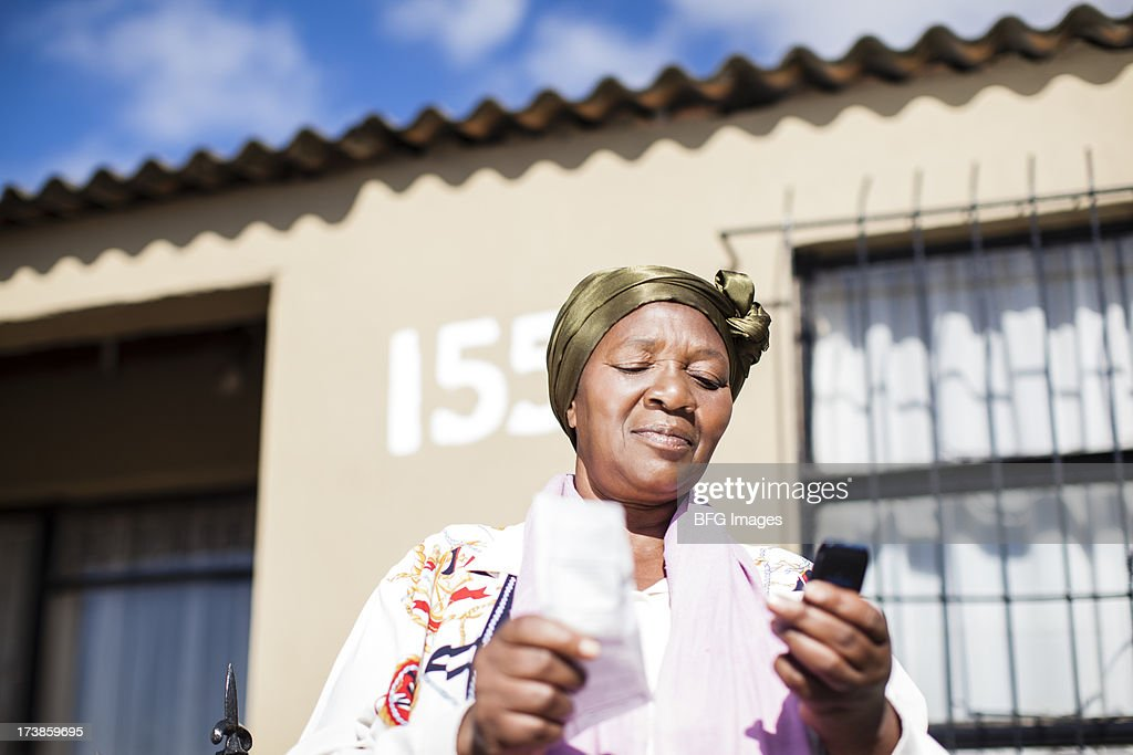 Woman holding cellphone and paper, Cape Town, South Africa. : Stock Photo