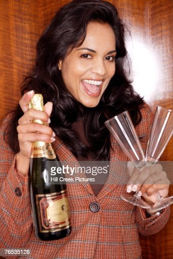 Woman holding champagne and champagne flutes