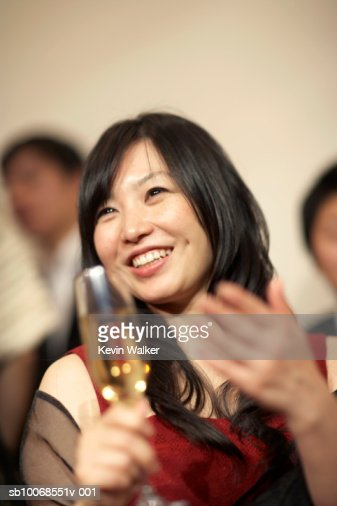 Woman holding champagne flute, smiling, close-up