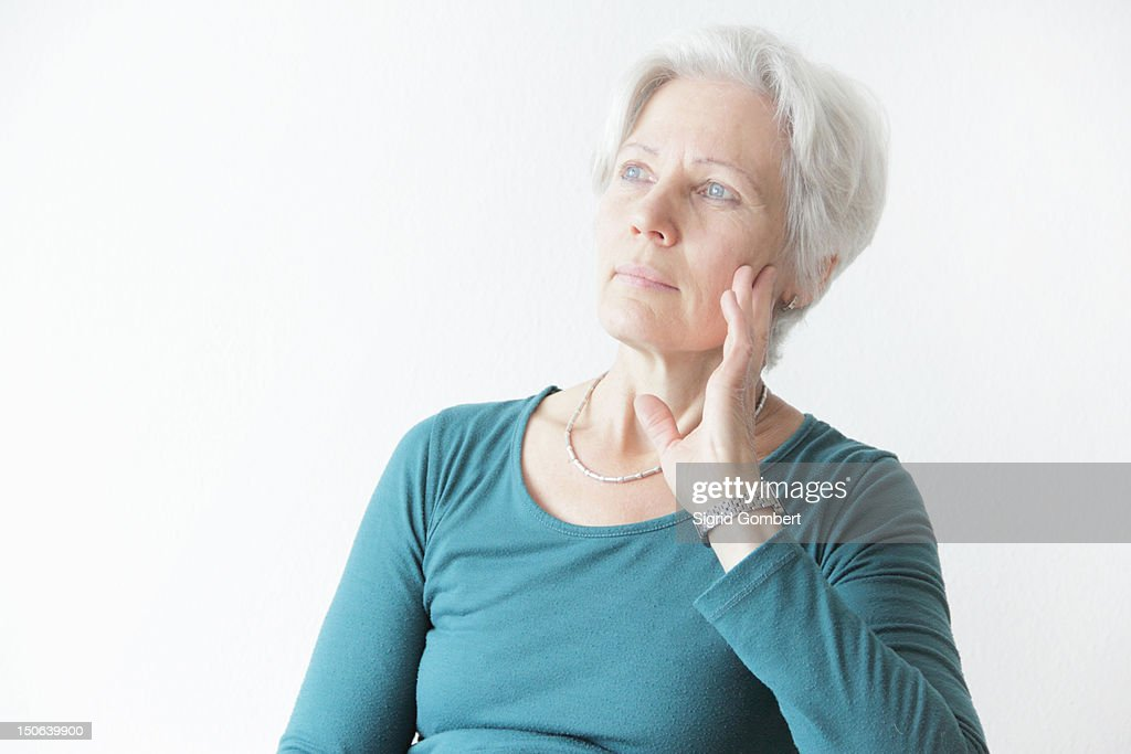Woman holding chin in hands : Stock Photo