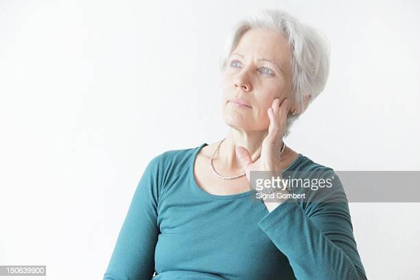 Mulher segurando o queixo nas Mãos