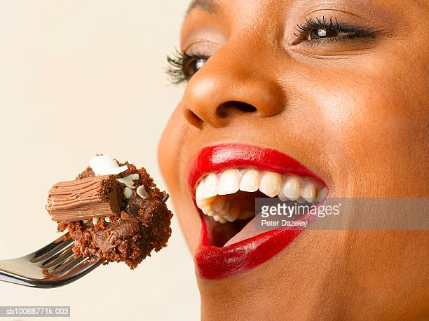 Woman holding chocolate cake on fork in front of mouth, close up, studio shot