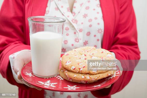 Woman holding Christmas cookies and glass of milk on plate