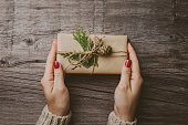 Woman holding christmas gift in craft paper on wooden table. View from above