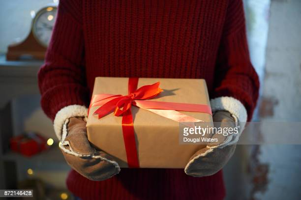 Woman holding Christmas present with red ribbon.