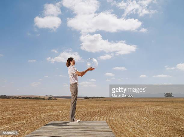 Woman holding clear globe on wooden dock