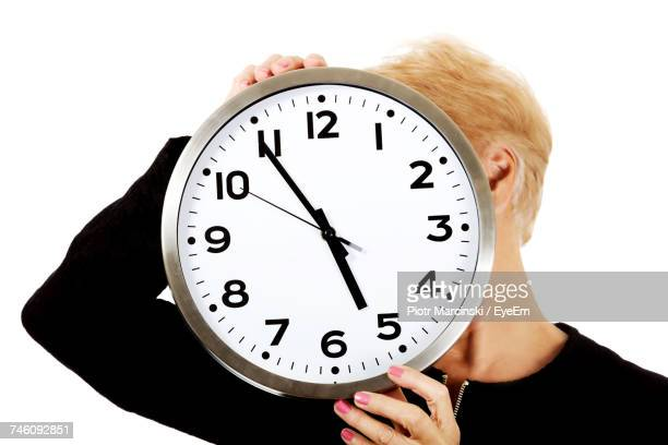 Woman Holding Clock In Front Of Face Against White Background