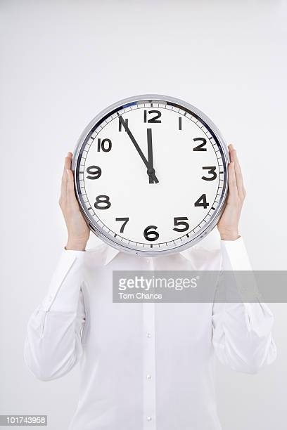 Woman holding clock in front of face