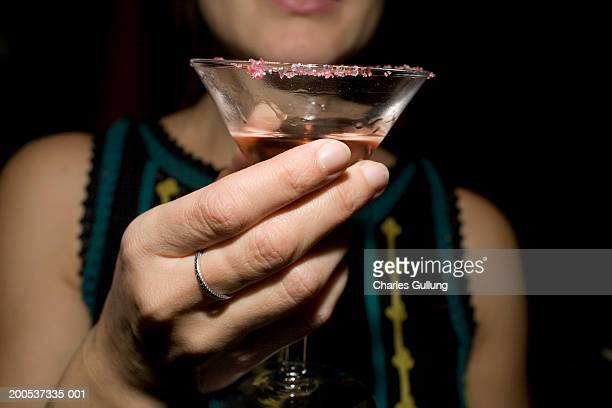 Woman holding cocktail in martini glass, mid section