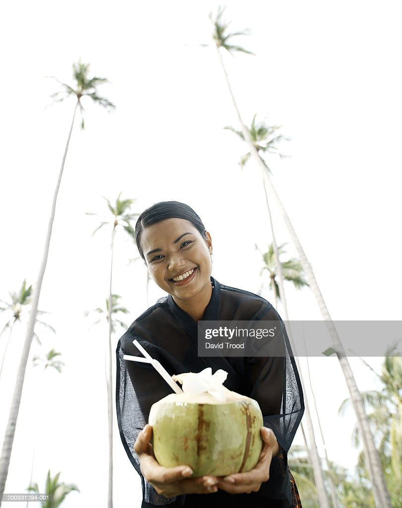 Woman holding coconut cocktail, smiling, portrait, low angle