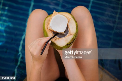 Femme tenant la noix de coco dans la piscine : Photo