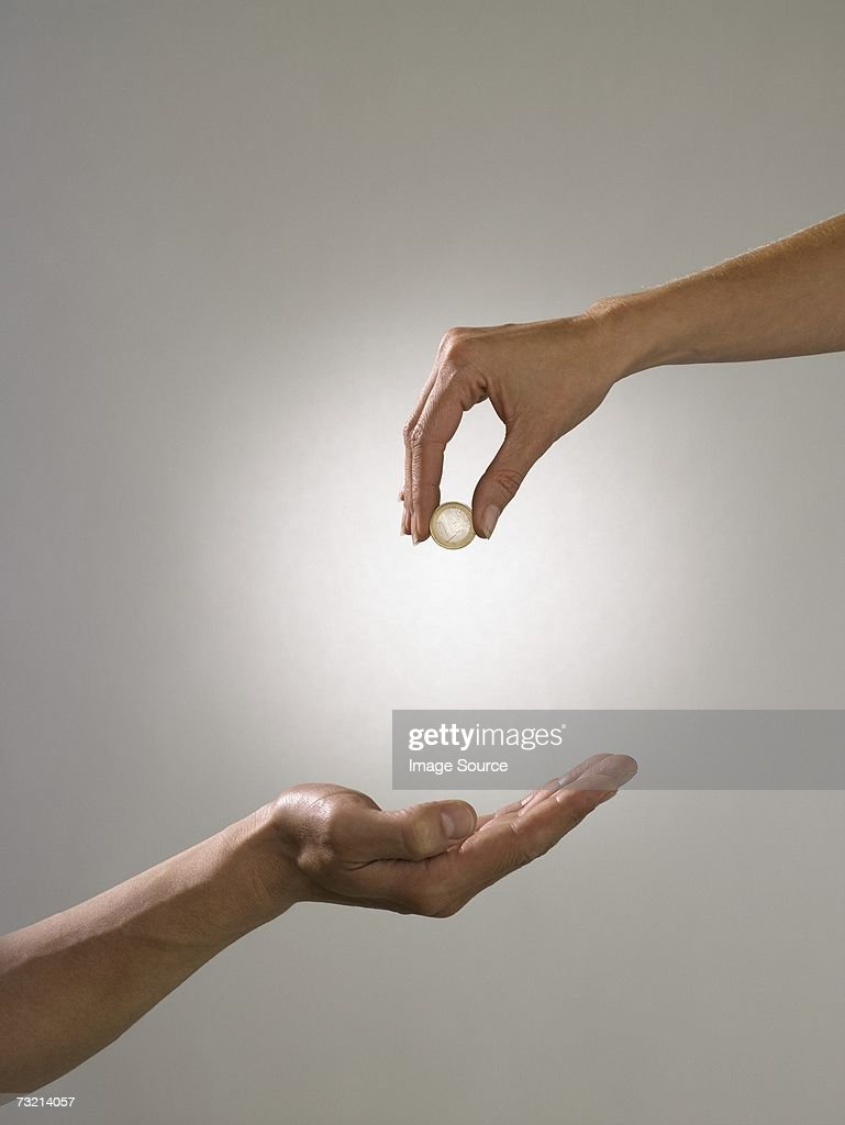 Woman holding coin above mans hand : Stock Photo