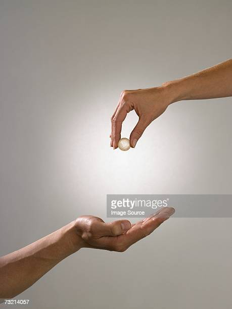 Woman holding coin above mans hand