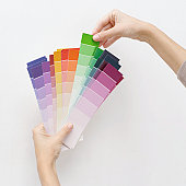 woman holding color shade cards