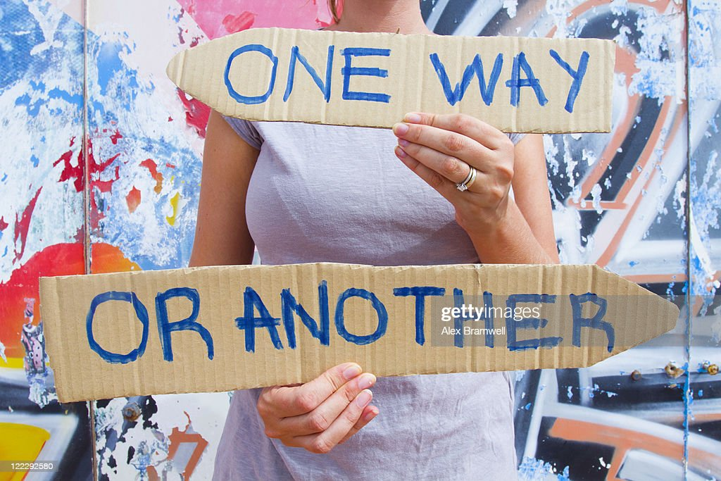 Woman holding conflicting direction signs : Stock Photo