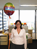 Woman holding 'congradulations' balloon in office, smiling, portrait