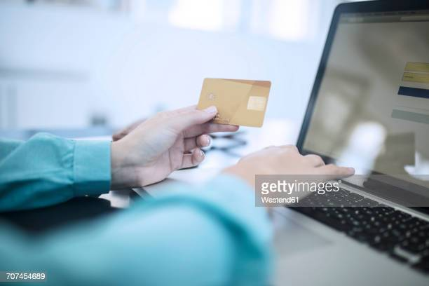 Woman holding credit card and typing on computer making an onliine payment