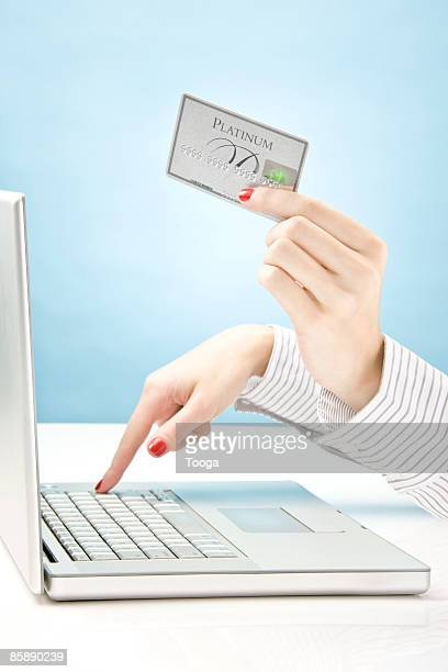 Woman holding credit card and using laptop