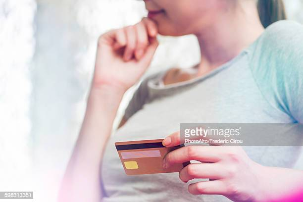 Woman holding credit card, cropped