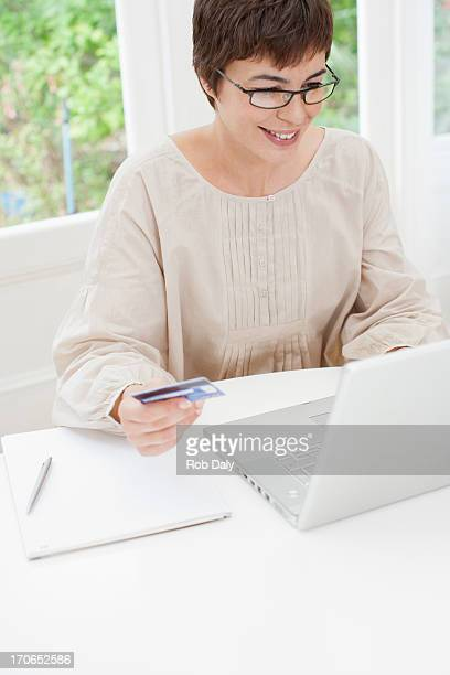 Woman holding credit card near laptop