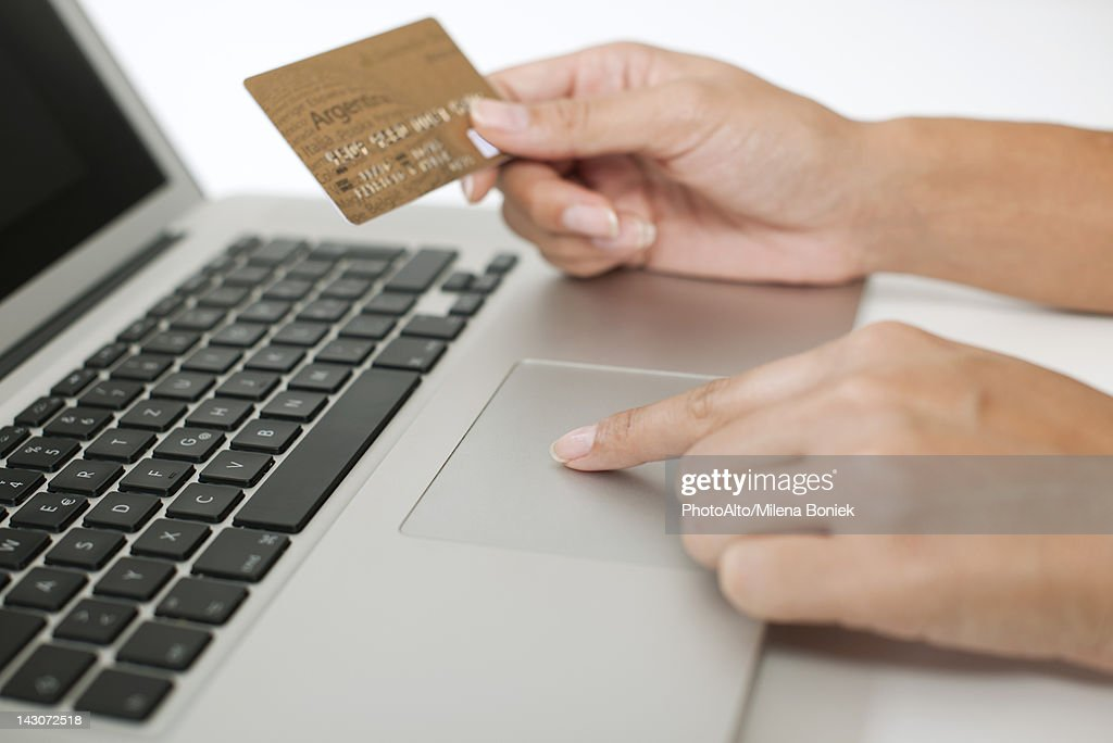 Woman holding credit card while using laptop computer, cropped : Stock Photo