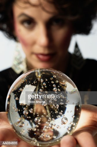Woman holding crystal ball, close-up (focus on ball) : Foto de stock
