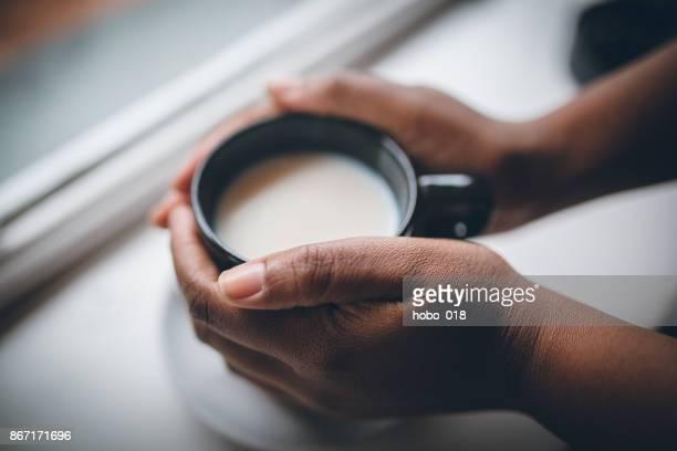 Frau mit Tasse Heißgetränk auf weißem Holz Hintergrund weiße Schokolade