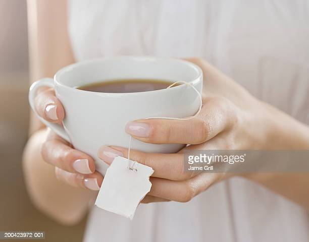 Woman holding cup of tea, close-up