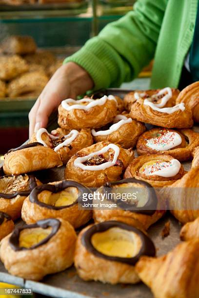 Woman holding Danish pastries in bakery