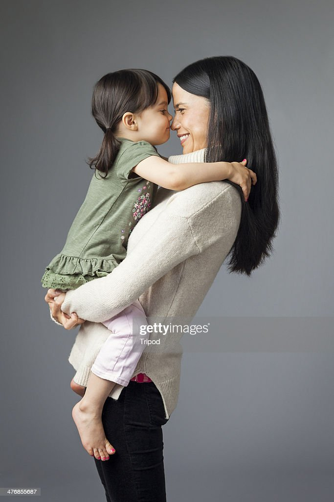 Woman holding daughter touching noses (2-4)