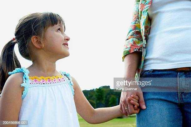 Woman holding daughter's (3-5) hand in park, girl smiling up at mother