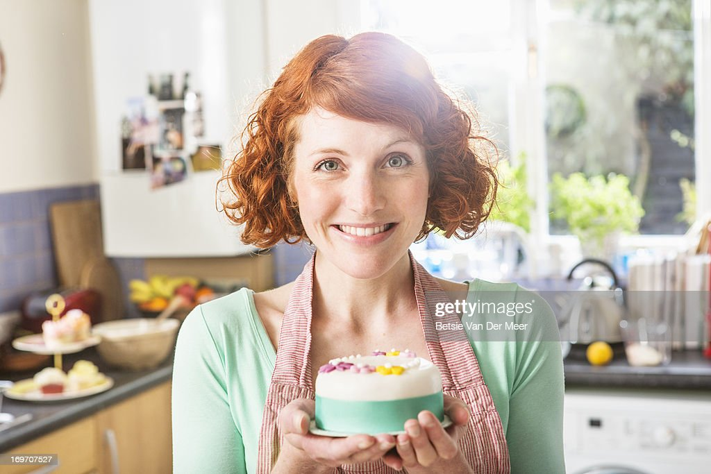 Woman holding decorated icing cake, in kitchen. : Stock Photo