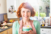 Woman holding decorated icing cake, in kitchen.