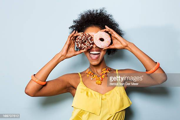 Woman holding different doughnuts in front of eyes