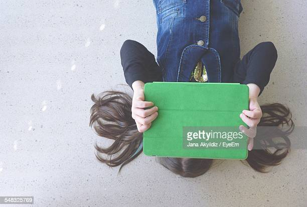Woman Holding Digital Tablet In Front Of Her Face