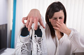 Woman Holding Dirty Stinky Shoes Covering Her Nose