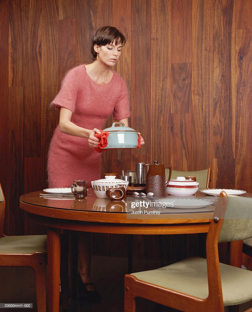 Woman holding dish above dinner table : Stock Photo