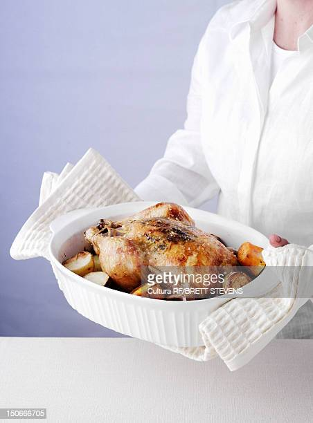 Woman holding dish of roast chicken