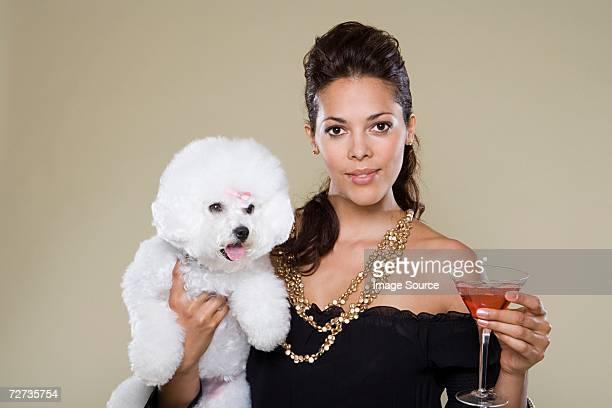 Femme tenant le chien et de cocktail en verre