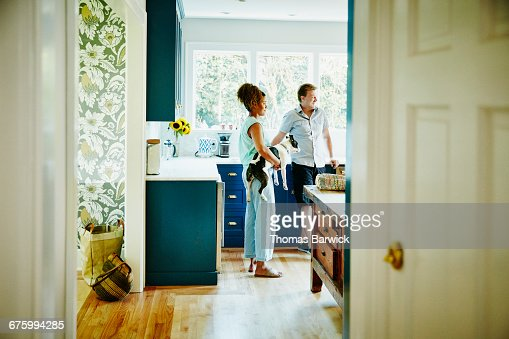 Woman holding dog hanging out in kitchen